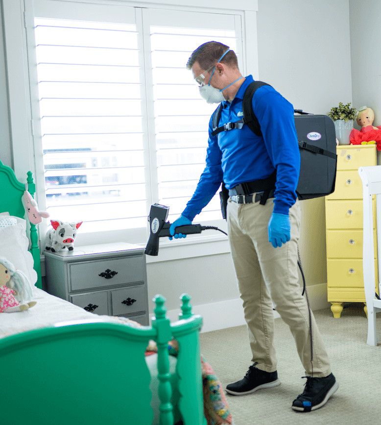 Man applying disinfectant in a bedroom